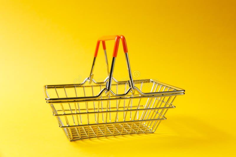 Sluit omhoog van de mand van de metaalkruidenierswinkel voor het winkelen in supermarkt met opgeheven geïsoleerde handvatten en o royalty-vrije stock afbeeldingen