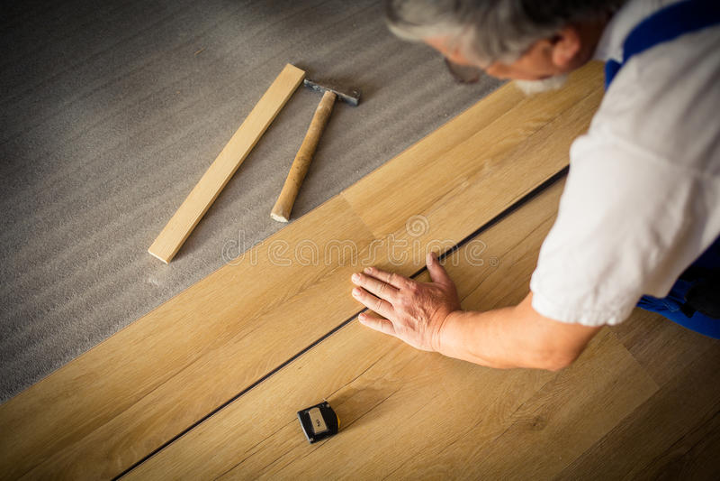 sluit omhoog van de mannelijke handen het liggen raad van de parketvloer stock foto's