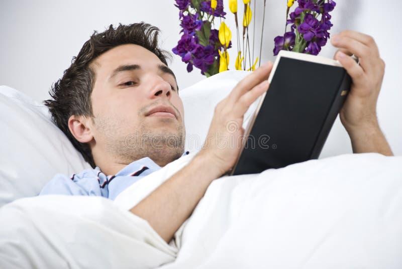 Sluit omhoog van de mens die een boek op bed leest royalty-vrije stock afbeeldingen