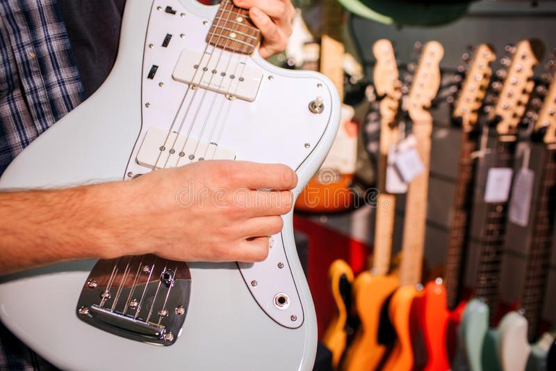 Sluit omhoog van de mens die lichtblauwe gitaar in handen houden Hij speelt op het en raakt zijn koorden Vele kleurrijke elektron stock foto's