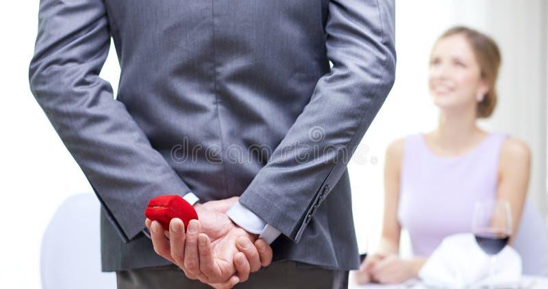 Sluit omhoog van de mens die rode doos erachter van vrouw verbergen royalty-vrije stock afbeeldingen