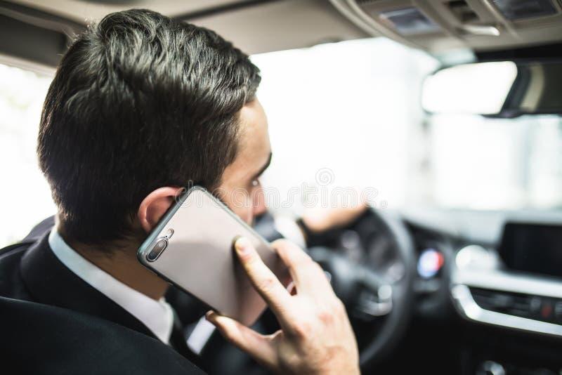 Sluit omhoog van de mens gebruikend smartphone terwijl het drijven van auto royalty-vrije stock afbeelding