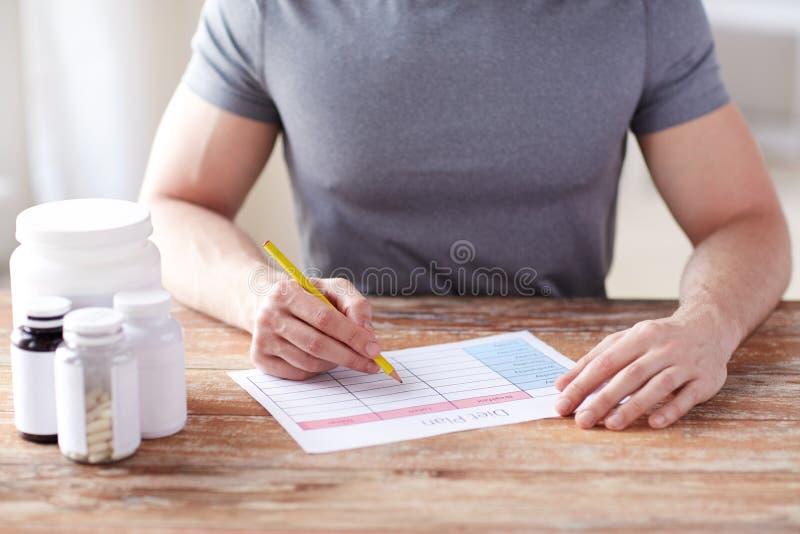 Sluit omhoog van de mens met eiwitkruiken en dieetplan royalty-vrije stock foto