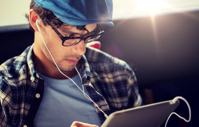 Sluit omhoog van de mens met tabletpc en oortelefoons royalty-vrije stock foto's