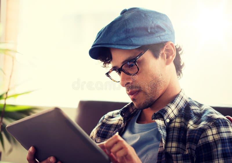 Sluit omhoog van de mens met de zitting van tabletpc bij koffie stock fotografie