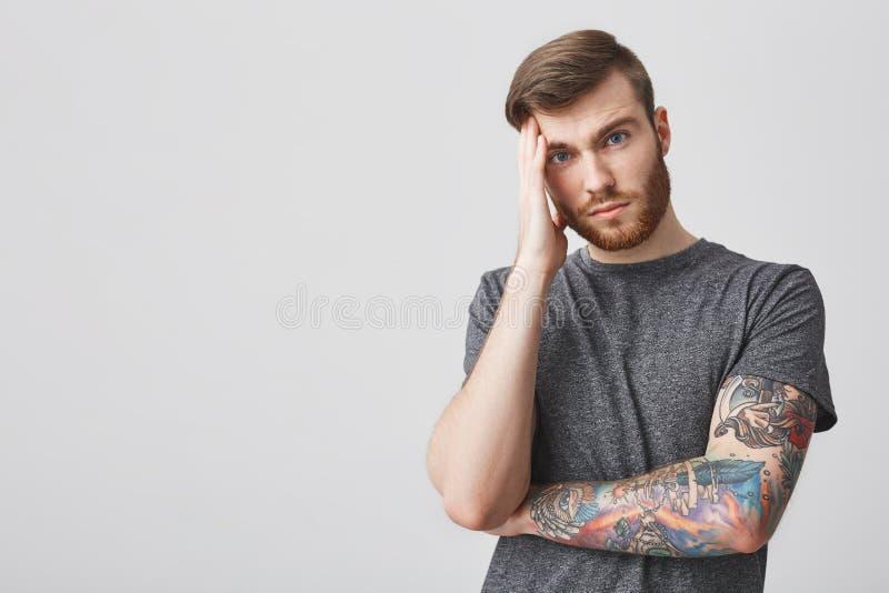 Sluit omhoog van de mooie ongelukkige gebaarde hipstermens met tatoegering en het goede hoofd van de kapselholding met hand, binn stock fotografie