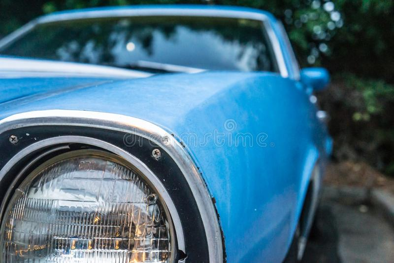 Sluit omhoog van de oude koplamp van de uitstekende blauwe auto Geparkeerd en omringd door bomen stock foto's