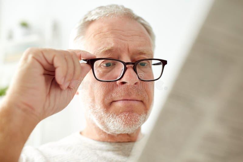 Sluit omhoog van de oude mens die in glazen krant lezen stock foto's