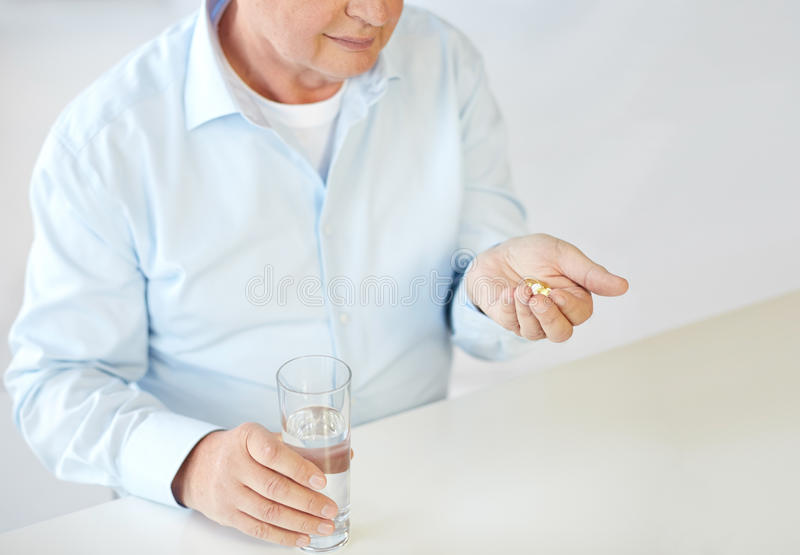 Sluit omhoog van de oude mens met pillen en waterglas royalty-vrije stock afbeeldingen