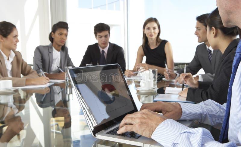 Sluit omhoog van de Raadsvergadering van Zakenmanusing laptop during rond stock fotografie