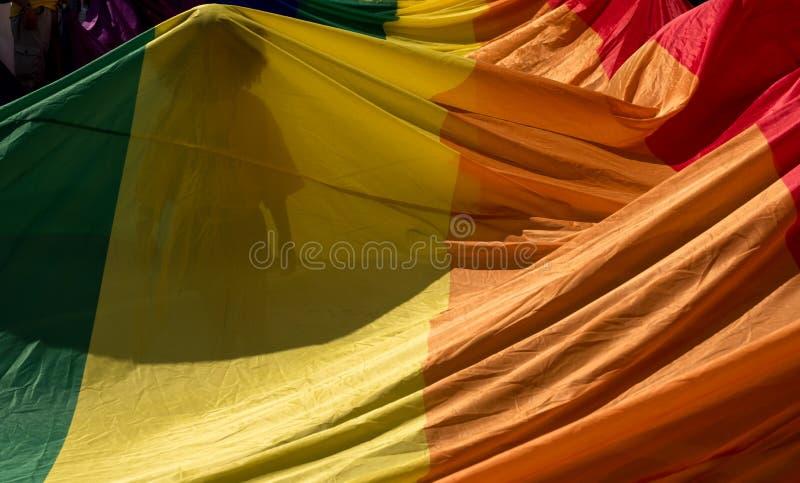 Sluit omhoog van de reuzeregenbooglgbt vlag Het silhouet van vrouw kan door de vlag zijn Gefotografeerd in sterk zonlicht royalty-vrije stock fotografie