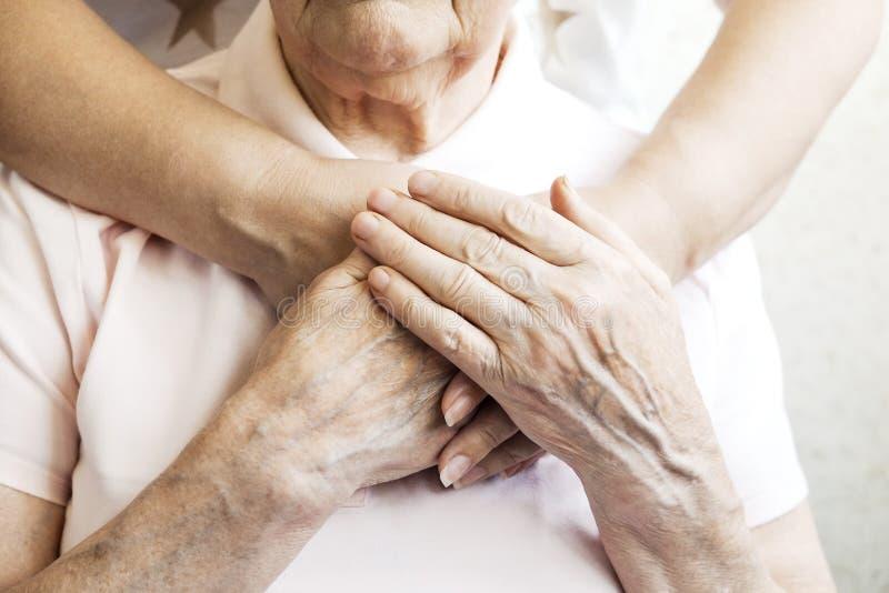 Sluit omhoog van de rijpe handen van de vrouw & van de verpleegster Gezondheidszorg die, verpleeghuis geven Ouderlijke liefde van stock foto