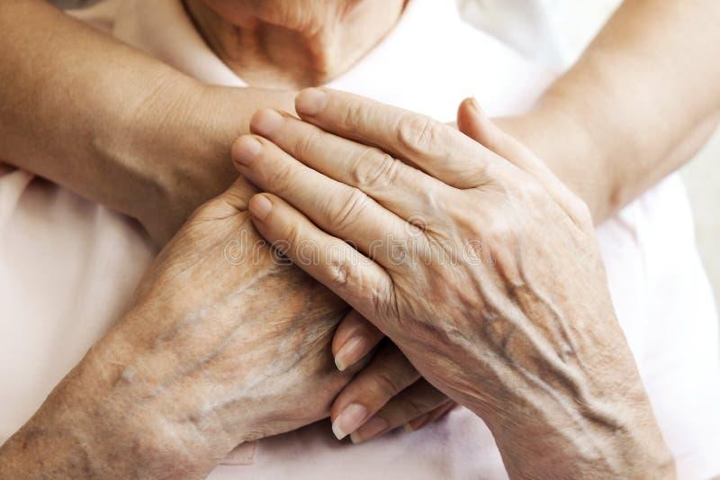 Sluit omhoog van de rijpe handen van de vrouw & van de verpleegster Gezondheidszorg die, verpleeghuis geven Ouderlijke liefde van stock foto's