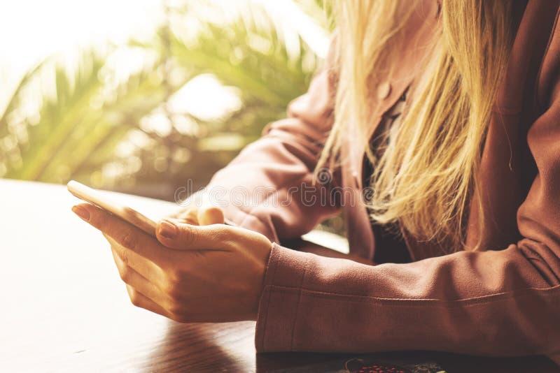 Sluit omhoog van de telefoon van de de handenbewaarcel van vrouwen met lege exemplaar ruimtepuinkegel voor uw reclamesms-bericht  royalty-vrije stock foto's