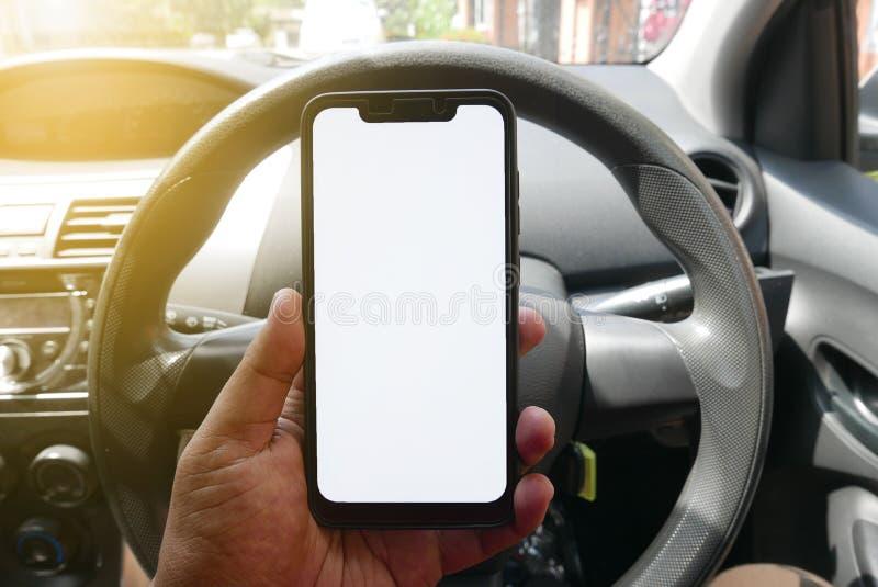 Sluit omhoog van de telefoon van de handholding met het witte scherm binnen een auto Smartphone met model op achtergrond van auto stock foto