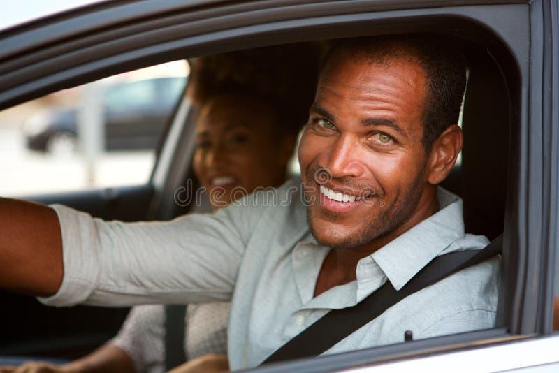 Sluit omhoog van de vrolijke mens en vrouw in auto op wegreis stock afbeeldingen