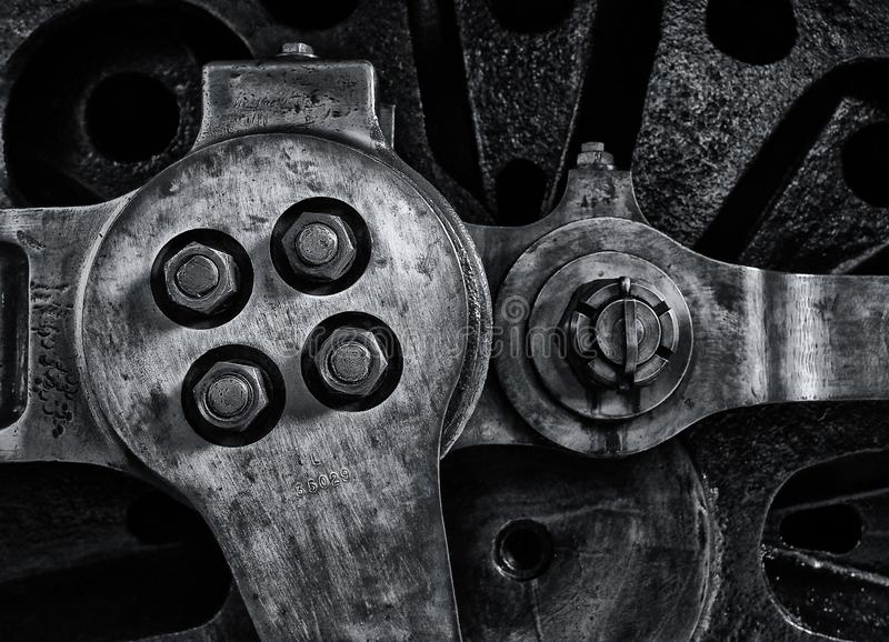 Sluit omhoog van de wiel en koppelingsstaven van een oude stoomlocomotief met geweven metaaloppervlakte en bouten royalty-vrije stock afbeelding
