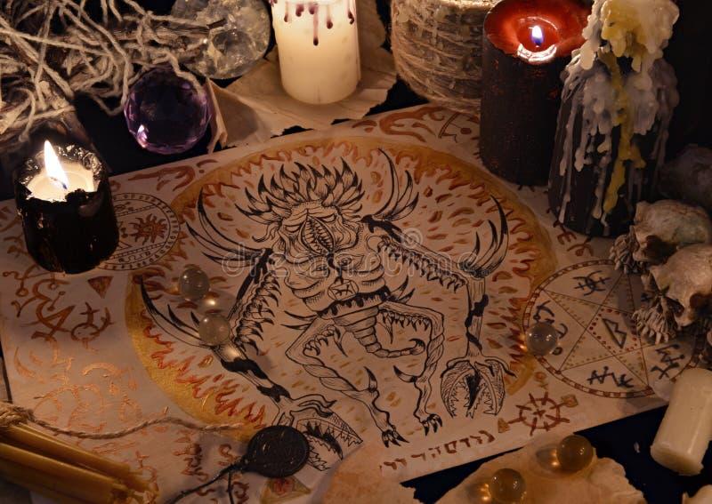 Sluit omhoog van demon die op oud perkament en magische rituele voorwerpen trekken stock fotografie