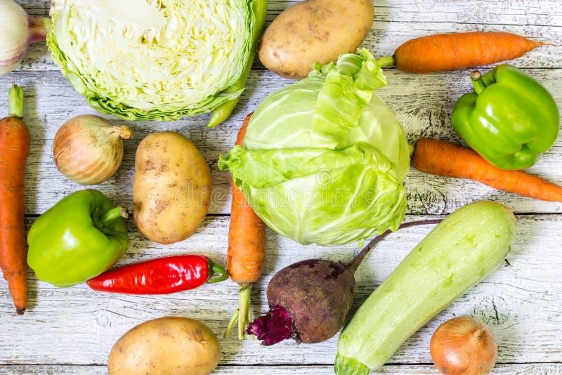 Sluit omhoog van diverse kleurrijke rauwe groenten op witte houten achtergrond royalty-vrije stock fotografie