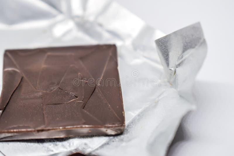 Sluit omhoog van Donker bruin die chocoladevierkant op zilveren folie op een witte achtergrond is gebarsten royalty-vrije stock afbeeldingen