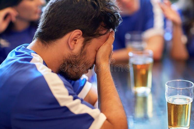 Sluit omhoog van droevige voetbalventilator bij bar of bar stock fotografie