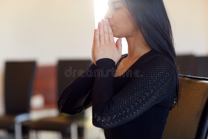 Sluit omhoog van droevige vrouwen biddende god in kerk royalty-vrije stock fotografie