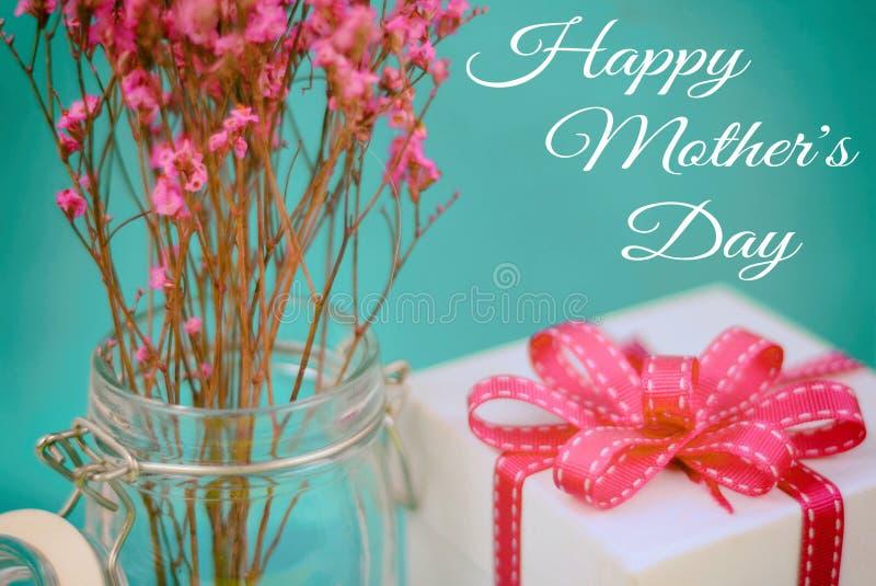 Sluit omhoog van droge roze bloemen in een hermetische kruik met een witte giftdoos en aanpassings roze lint op een blauwe achter royalty-vrije stock foto