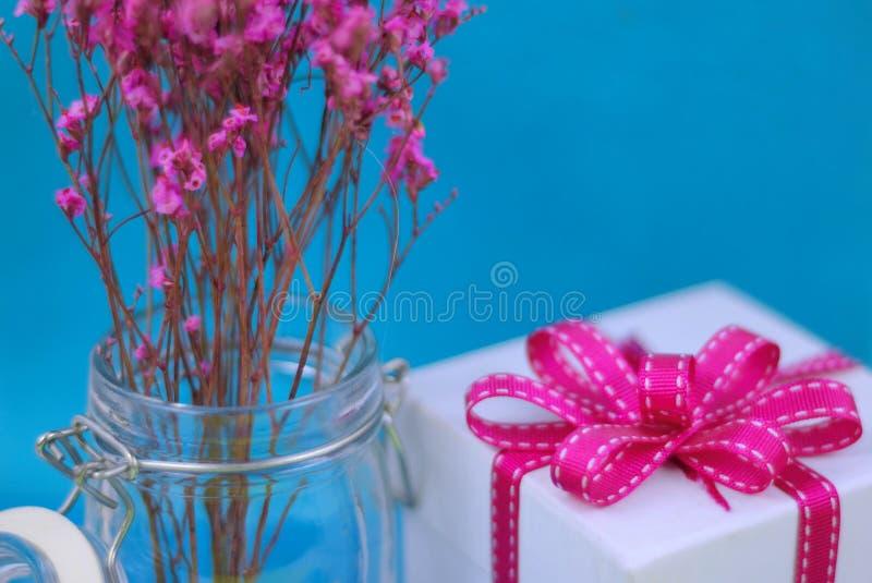 Sluit omhoog van droge roze bloemen in een hermetische kruik met een witte giftdoos en aanpassings roze lint op een blauwe achter stock afbeeldingen