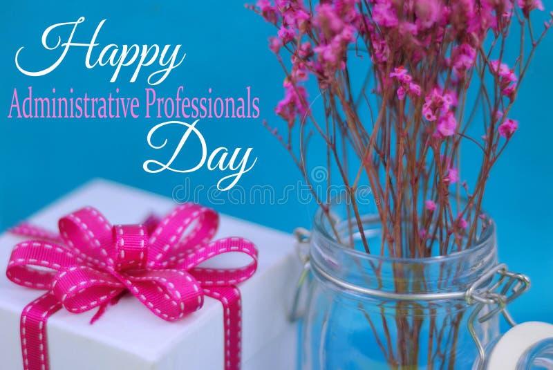 Sluit omhoog van droge roze bloemen in een hermetische kruik met een witte giftdoos en aanpassings roze lint op een blauwe achter stock fotografie