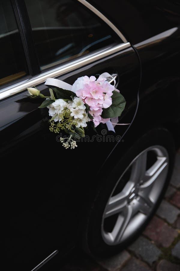 Sluit omhoog van echte bloemendetails bij een huwelijk - Autodecoratie van een bruidegom en een bruid stock fotografie