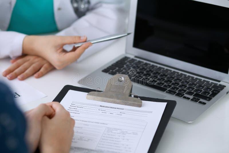 Sluit omhoog van een arts en een geduldige zitting bij het bureau terwijl arts het richten in laptop computer De geneeskunde en h stock foto's