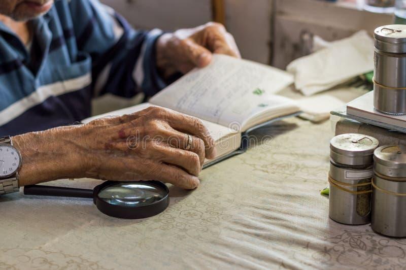 Sluit omhoog van een bejaardehand houdend een notitieboekje dichtbij het venster in de keuken royalty-vrije stock afbeeldingen