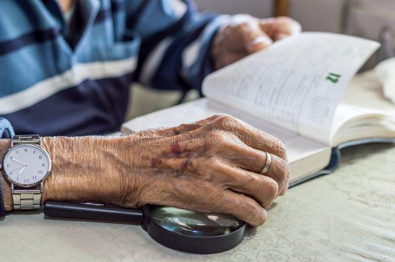 Sluit omhoog van een bejaardehand houdend een notitieboekje dichtbij het venster in de keuken stock afbeelding