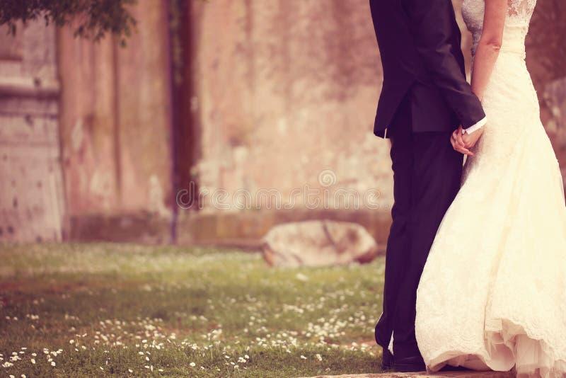 Sluit omhoog van een bruid en bruidegomholdingshanden stock afbeeldingen