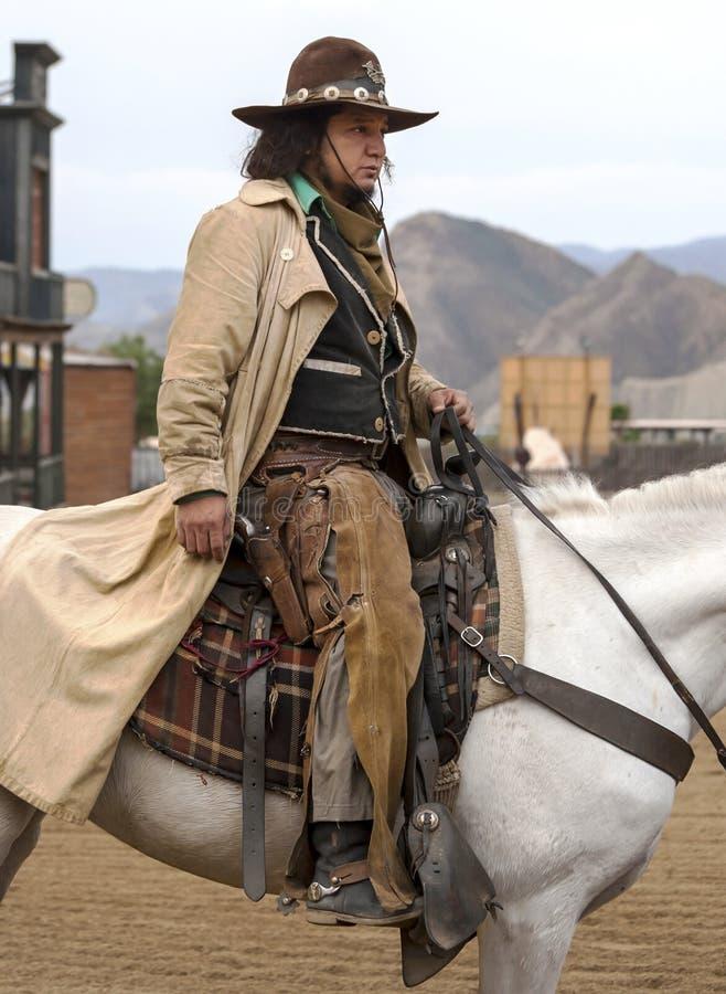 Sluit omhoog van een Cowboy die zijn paard berijdt in stad stock afbeelding