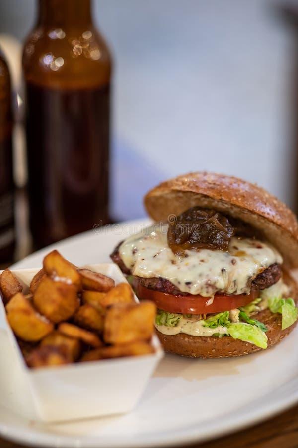 Sluit omhoog van een eigengemaakte hamburger met kruidige aardappels royalty-vrije stock foto's