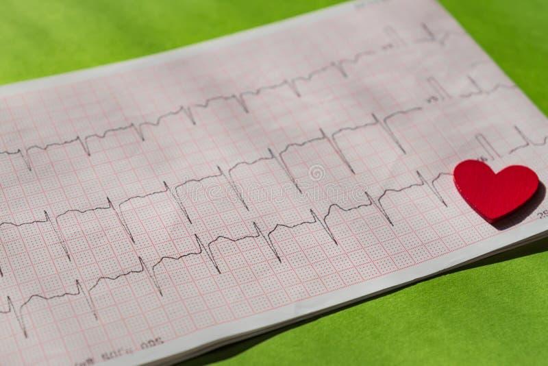 Sluit omhoog van een elektrocardiogram in document vorm vith rood houten hart Het document van ECG of van het electrocardiogram o stock foto's