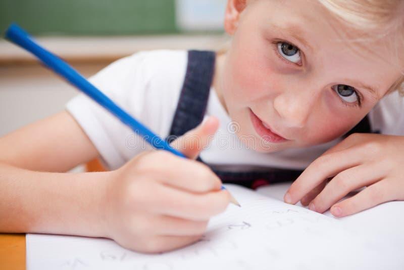 Sluit omhoog van een ernstig schoolmeisje die iets schrijven royalty-vrije stock foto