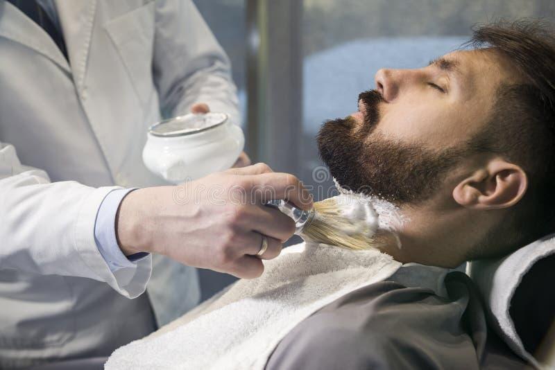 Sluit omhoog van een gebaarde bruine haired zakenmanzitting bij een kapperswinkel als voorzitter stock fotografie