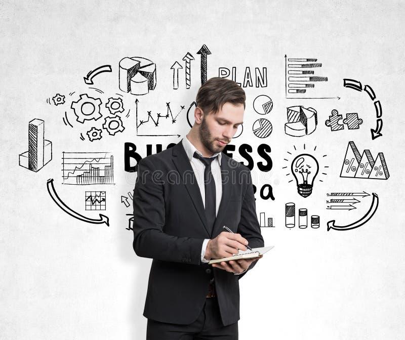 Sluit omhoog van een gebaarde zakenman die met een notitieboekje terwijl status dichtbij een concrete muur schrijven stock fotografie
