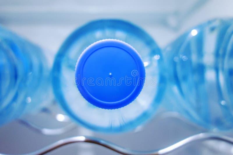 Sluit omhoog van een gebotteld water in een ijskast stock foto