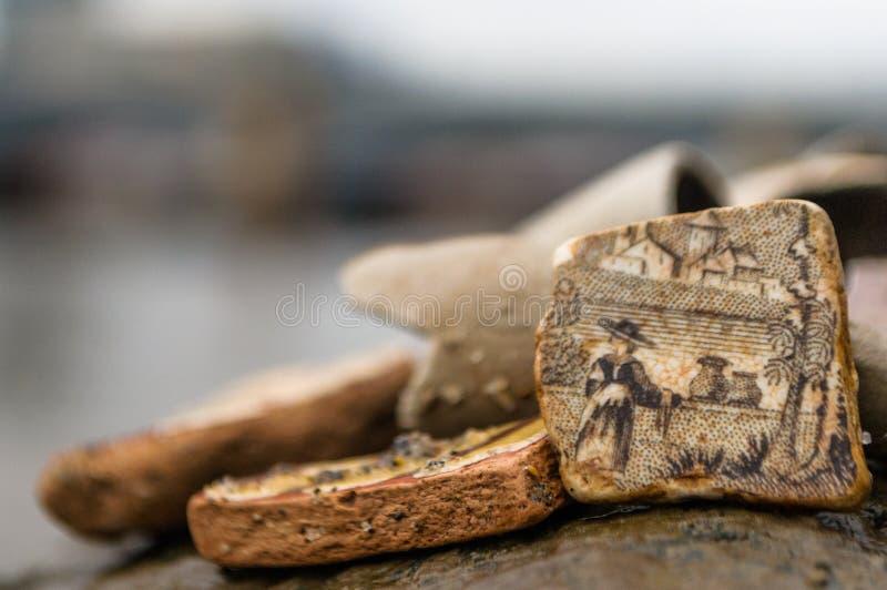 Sluit omhoog van een gedetailleerd stuk van oud gebroken die aardewerk langs een rivier wordt gevonden stock foto's