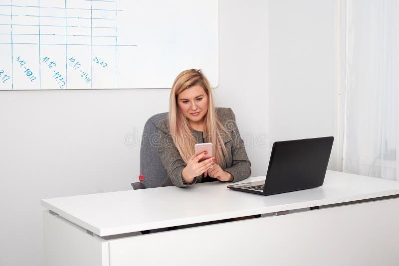 Sluit omhoog van een geinteresseerde onderneemster in een kostuum die op haar wit kantoor werken Zij spreekt op telefoon en het w royalty-vrije stock afbeeldingen