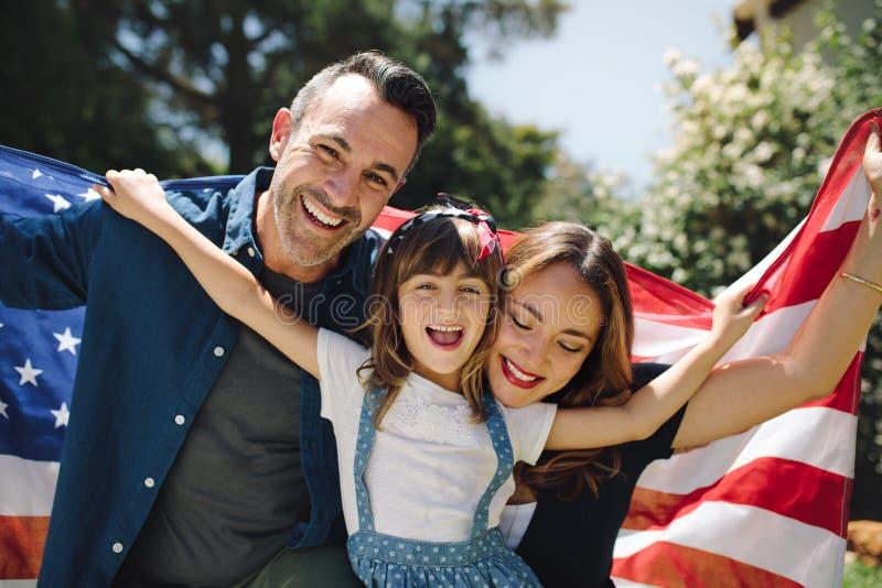 Sluit omhoog van een gelukkige familie die de Amerikaanse vlag houden stock afbeeldingen