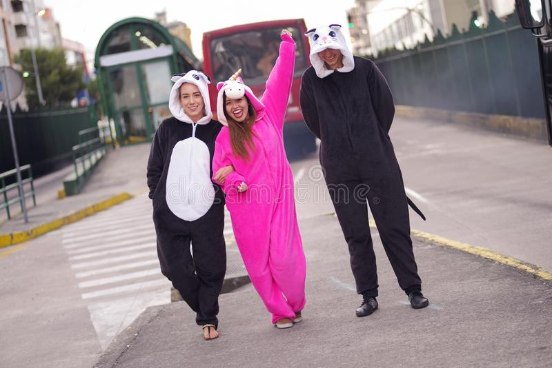 Sluit omhoog van een gelukkige groep vrienden die verschillende kostuums dragen, één vrouw die een roze eenhoornkostuum, andere v stock fotografie