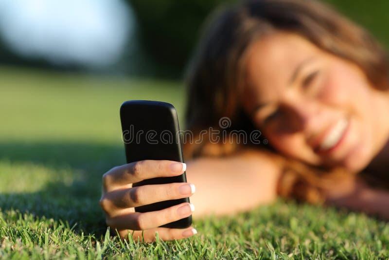 Sluit omhoog van een gelukkige hand van het tienermeisje gebruikend een slimme telefoon op het gras royalty-vrije stock foto's
