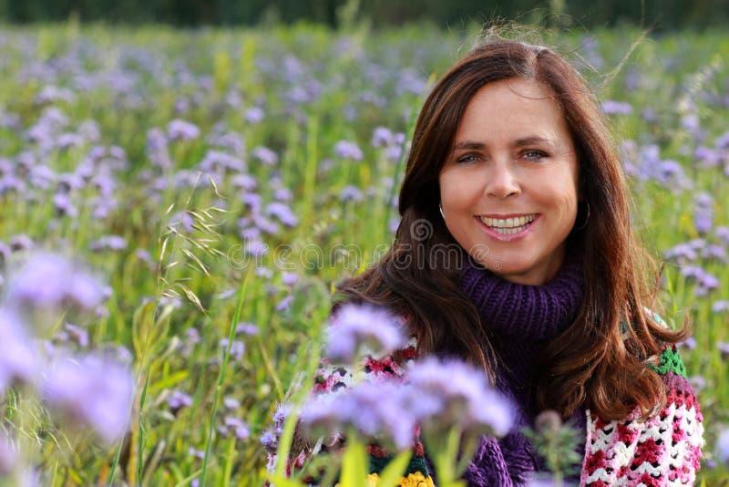 Sluit omhoog van een gelukkige rijpe vrouw op een bloemgebied stock afbeeldingen