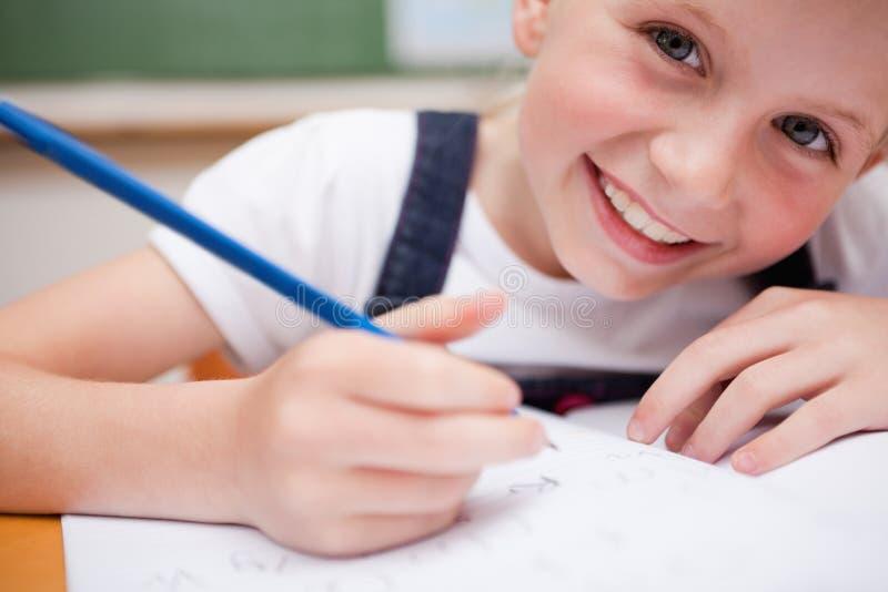 Sluit omhoog van een glimlachend schoolmeisje die iets schrijven royalty-vrije stock afbeelding
