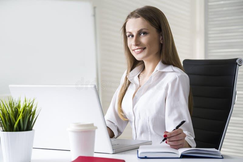 Sluit omhoog van een glimlachende en mooie onderneemster die een witte blouse dragen en bij haar bureau met laptop zitten stock afbeelding