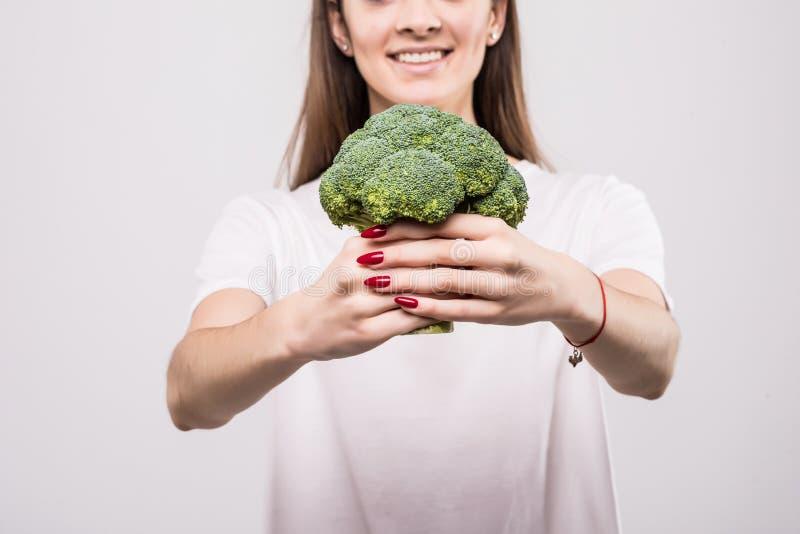 Sluit omhoog van een glimlachende vrouw die die broccoli tonen over witte achtergrond worden geïsoleerd Het concept van de gezond stock afbeeldingen